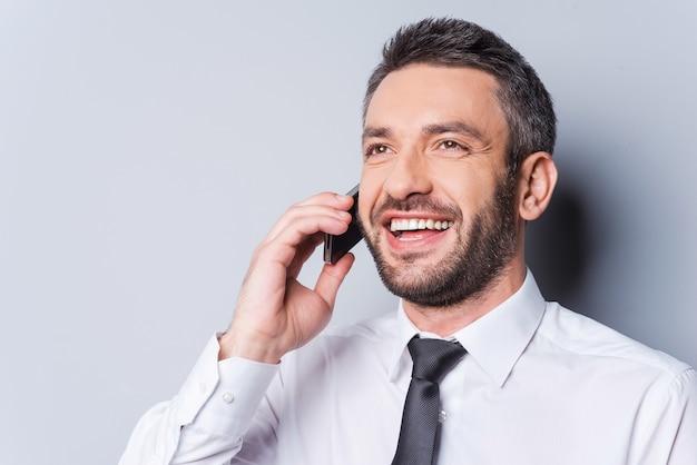 좋은 소식! 셔츠를 입고 넥타이를 매고 휴대폰으로 통화하고 회색 배경에 서서 웃고 있는 행복한 성숙한 남자
