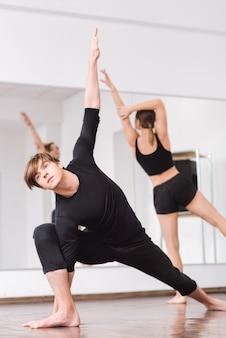 Отличная пластичность. симпатичный красивый молодой человек, держащий одну руку и касающийся пола другой, выполняя физическое упражнение