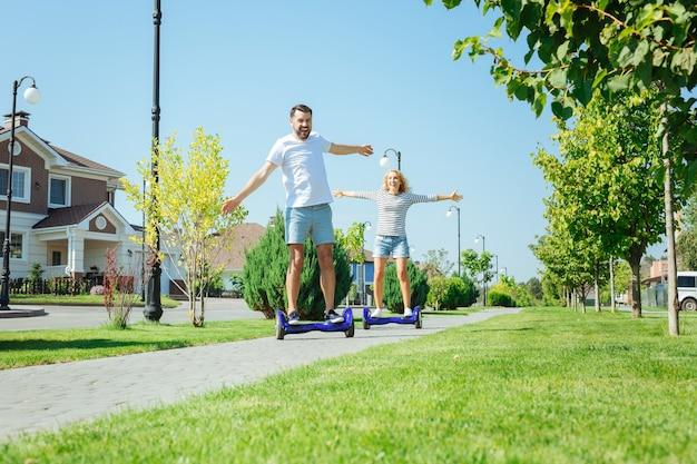 Большое удовольствие. возбужденные молодые муж и жена катаются на ховербордах по тротуару и широко разводят руками, наслаждаясь поездкой