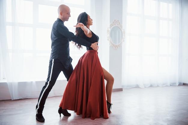 Grandi prestazioni professionali. giovane donna graziosa in vestiti rossi e neri che ballano con il ragazzo calvo nella stanza bianca