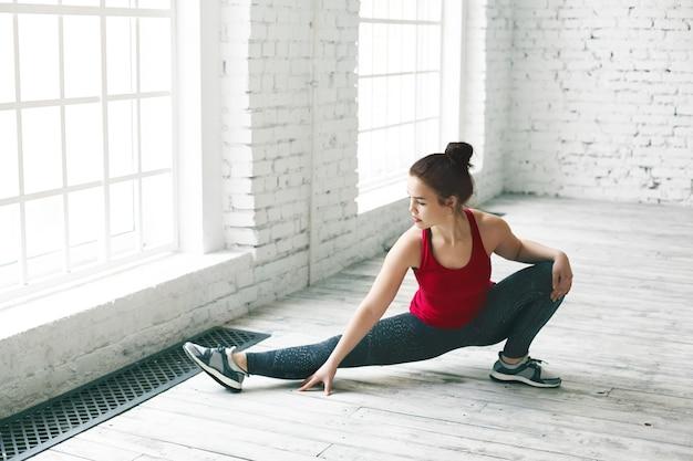 大きな進歩。魅力的な若いヨーロッパ人女性が屋内でストレッチをし、広告コンテンツ用のコピースペースの壁があるライトホールでサイドスプリットの前に脚の筋肉を温めている写真