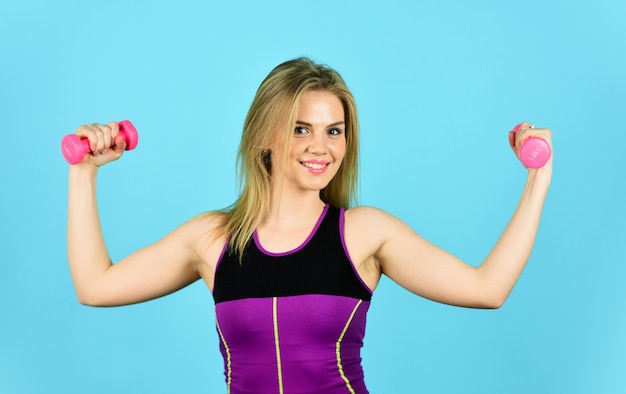 Great progress. slim girl doing triceps exercise with dumbbell in the gym. coach dressed in sport clothes. muscular woman in training pumping up muscles of hands. girl use barbell blue background.