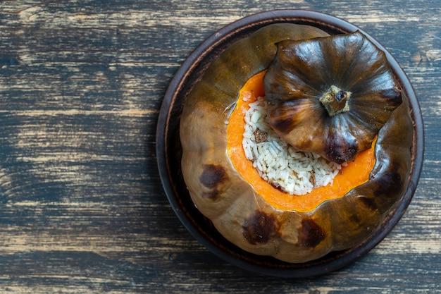 プレート、上面図、コピースペースに詰め物のクローズアップで焼いた素晴らしいカボチャ。焼きたてのオレンジカボチャのロースト、ご飯、レーズン、スパイスのおいしい混合物を詰めたもの