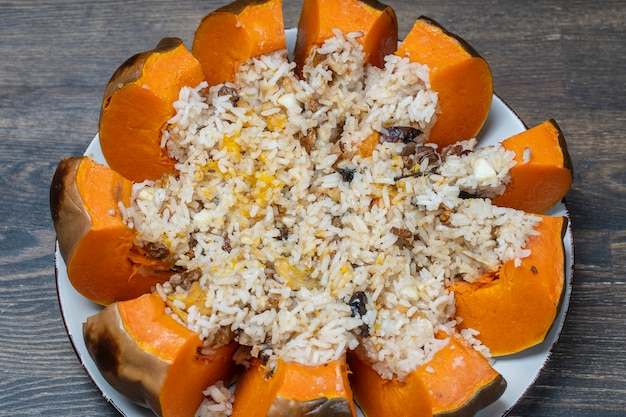 皿に詰め物のクローズアップで焼いたカボチャ大王、上面図。焼きたてのオレンジ色のカボチャの詰め物、ご飯、レーズン、スパイスのおいしい混合物でいっぱい
