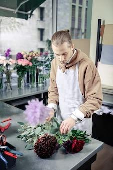 素晴らしい品質。職場に立って異常な花を見ている真面目な男性