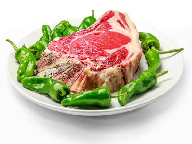 Great raw cutlet of cow with green peppers on plate and white