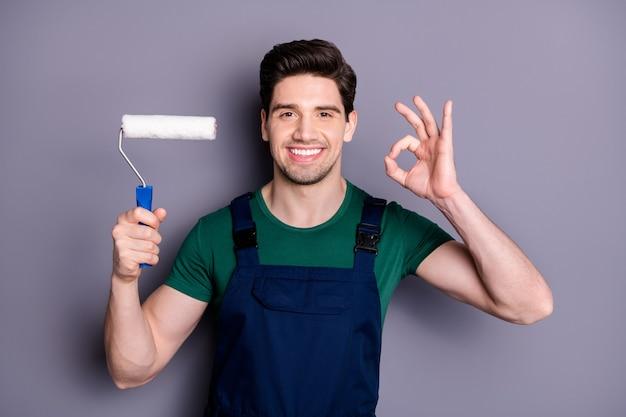 Отличная концепция реконструкции. позитивный крутой мастер художник держит белый ролик обновить дом рекомендую показать знак ок носить зеленую футболку синюю униформу изолированный серый цвет стена