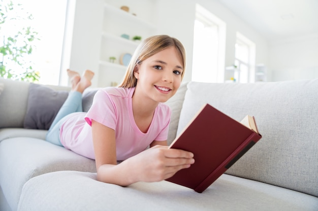 Great remote study concept. full size photo of positive kid pupil girl lying comfy divan read interesting textbook prepare school project in house indoors