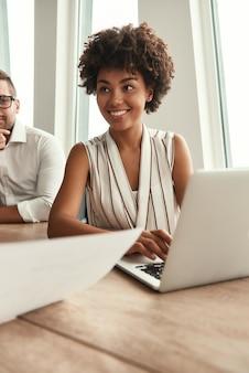 Отличные результаты молодая и красивая афро-американская женщина работает на ноутбуке и смотрит с улыбкой, сидя за офисным столом. деловая встреча. мозговой штурм