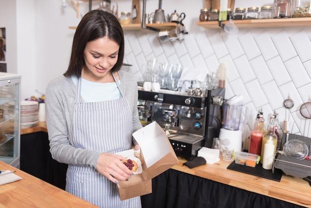 素晴らしいサービス。コーヒーショップのカウンターの後ろで働いている間、美しく魅力的な陽気なウェイトレスは微笑んで、箱にケーキを注意深く包装します。