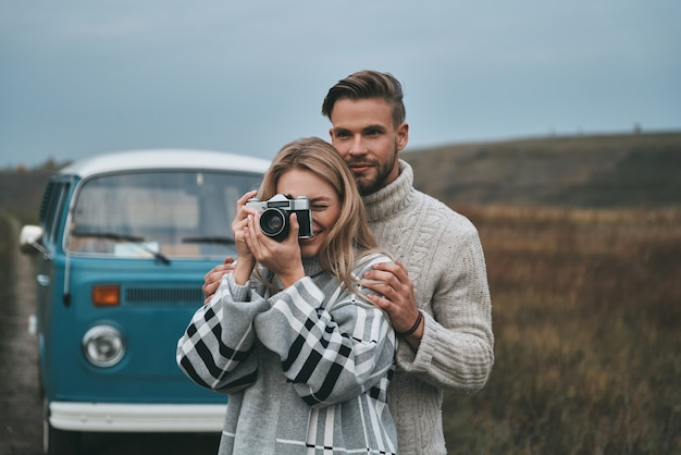 Great shot! beautiful young woman photographing and smiling while standing with her boyfriend outdoors