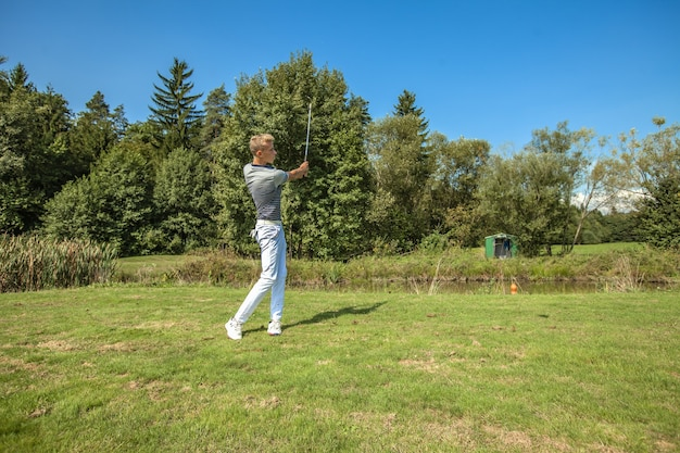 Great shot of a young man playing golf in a field surrounded by trees on a sunny day