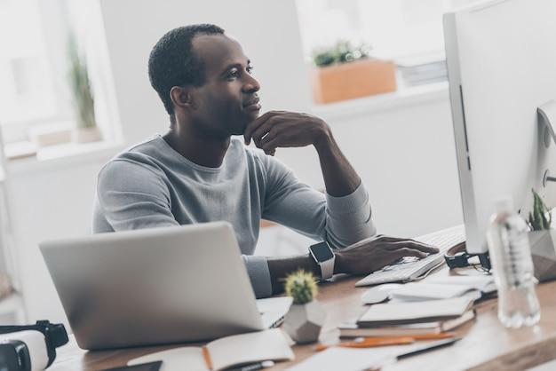 Отличные решения каждый день. красивый молодой африканский мужчина держит руку к лицу, сидя на своем рабочем месте в домашнем офисе