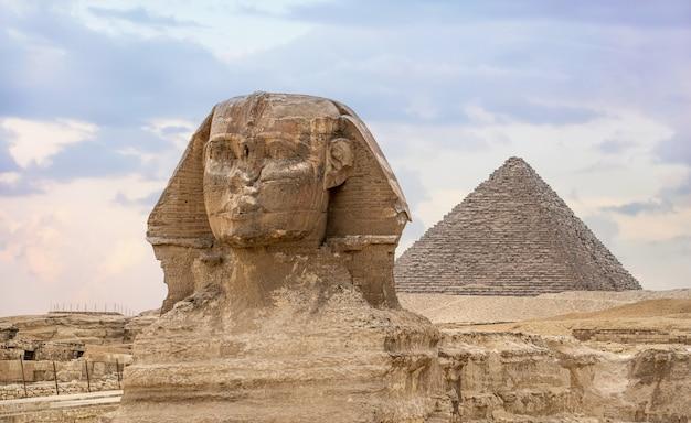 위대한 스핑크스와 카프레의 피라미드. 고대 이집트 문명. 이집트 피라미드가 있는 풍경. 황금빛 햇빛 속에서 아프리카로의 여행 개념을 위한 이집트의 고대 상징과 랜드마크.