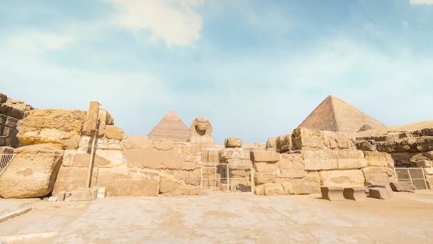 エジプト、カイロ、ギザの美しい青空の日にピラミッドを背景にした素晴らしいスフィンクス。