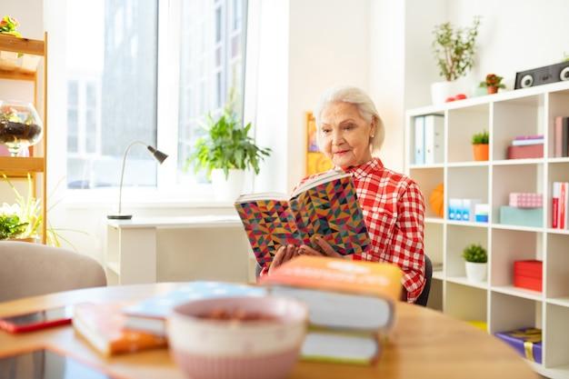 Отличная история. милая позитивная женщина сидит за столом и читает интересную книгу