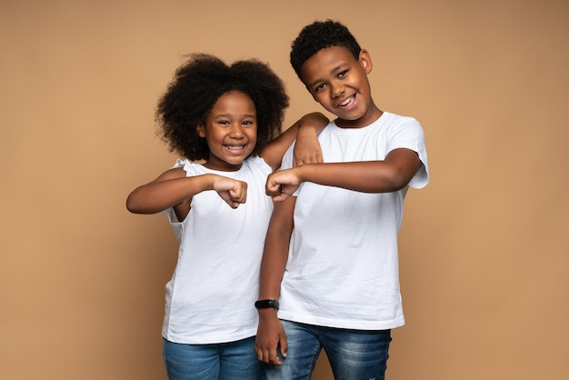 Great team. portrait of positive brother and sister hugging and bumping with fists with toothy smile, while posing to the camera. isolated, indoor, studio shot, beige background