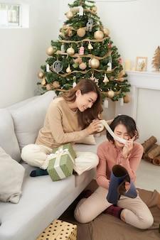 クリスマスのプレゼントを詰める友達の素晴らしいチームワーク