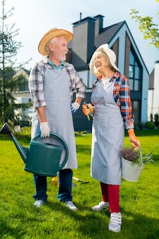 素晴らしい時間です。庭で時間を過ごしながら幸せを感じている元気な引退したカップル