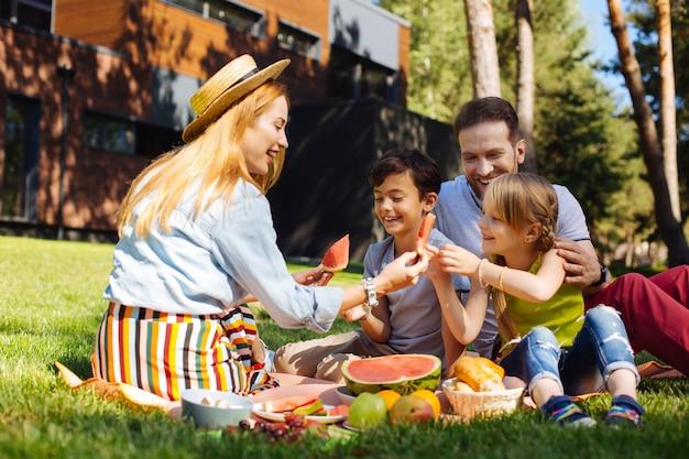 함께 즐거운 시간을 보내십시오. 웃 고 그녀의 아이들에게 수박을주는 쾌활한 젊은 어머니