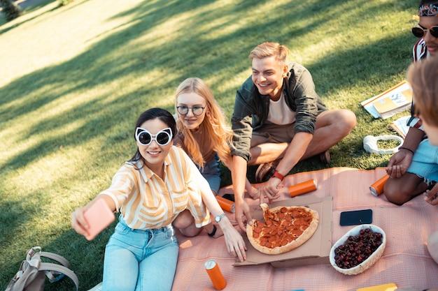 Прекрасное время с друзьями. веселые друзья сидят на траве, делают селфи и едят пиццу после выполнения своей домашней работы.