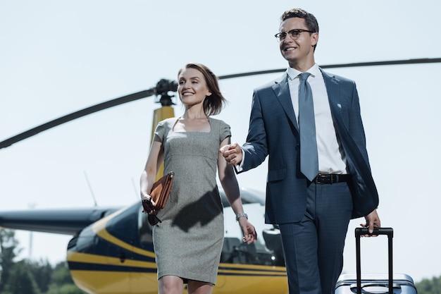 素晴らしい旅行。一緒にヘリコプターから離れて、元気に笑って、出張を終えた幸せな若いカップル
