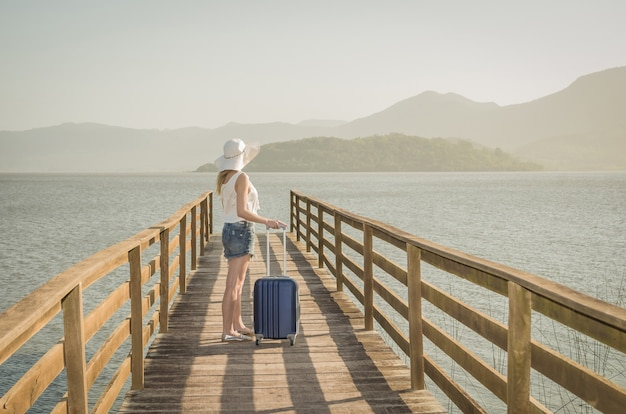 Great vacation concept. young woman holding her suitcase, waiting for the boat on the dock
