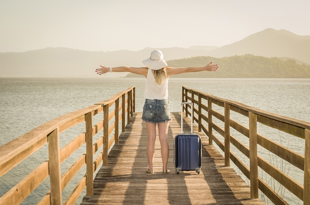 Great vacation concept. young woman with open arms and suitcase waiting for the boat on the dock
