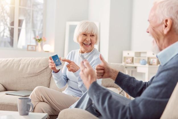 素晴らしい天気。陽気な老夫婦がリビングルームのソファに座って、天気アプリをチェックして親指を表示し、天気に満足している