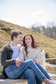 素晴らしい週末。晴れた日に自然の中でベンチに座ってカジュアルな服を着た女性に触れるうれしそうな若い男笑顔