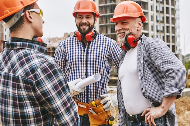 보호복과 빨간 헬멧을 쓴 훌륭한 작업 그룹이 새로운 프로젝트에 대해 논의하고 있습니다