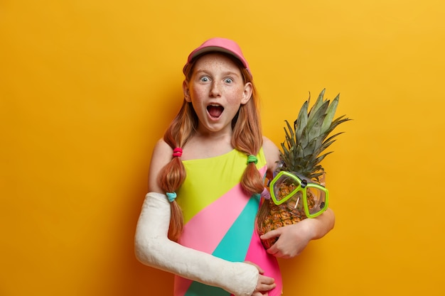 Greatly impressed freckled girl stands with widely opened mouth, embraces pineapple with snorkeling mask, enjoys summer time, has broken arm, isolated on yellow wall. children, emotions