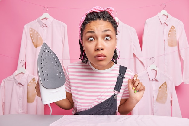 Greatly surprised ethnic woman with braids stares shocked at camera busy ironing at home holds electric irond dressed in casual clothes does daily domestic chores stands against ironed shirts