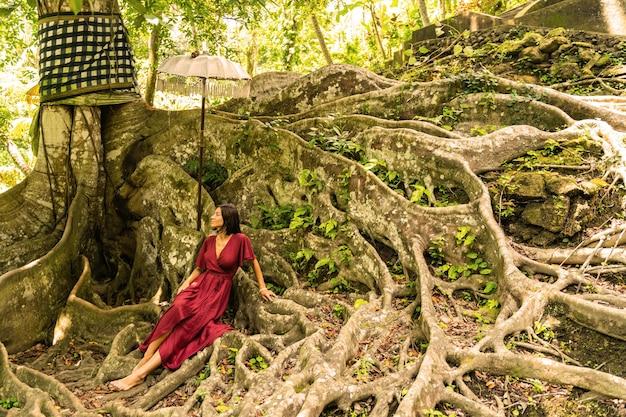 자연의 위대함. 큰 나무 근처에서 휴식을 취하는 동안 그녀의 생각에 깊이 있는 귀여운 갈색 머리 소녀