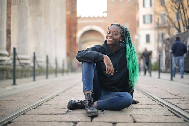 Молодая женщина с gree косами, сидя на улице