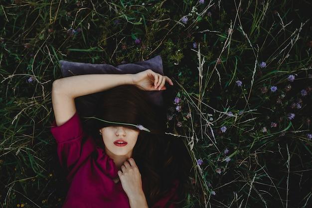 Женский портрет. очаровательная женщина в фиолетовой рубашке лежит на gree