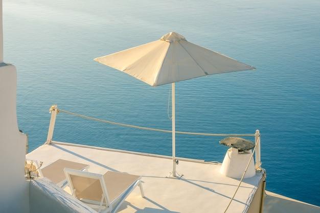 그리스. 산토리니의 조용한 여름 저녁. 바다 전망의 발코니에 있는 2개의 일광욕용 라운저와 우산