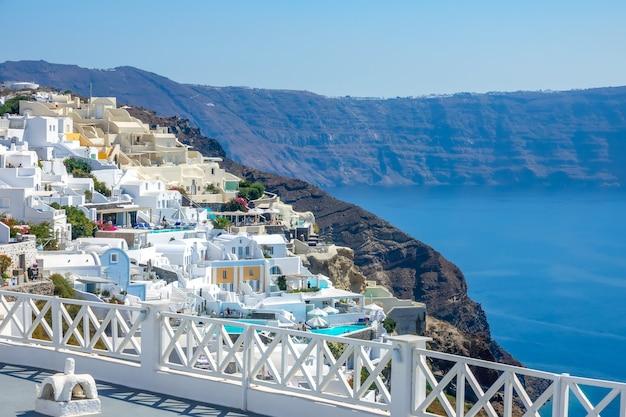 ギリシャ。サントリーニ島のカルデラの晴れた夏の日。岩の多い海岸と青い海。エメラルドの水とオイアの白い家とプール