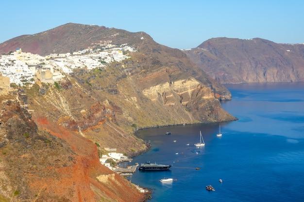 Греция. залив в кальдере острова санторини в солнечный день. деревня ия на склоне скалистого берега. несколько парусных и моторных яхт