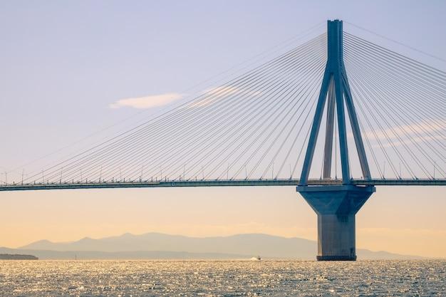 ギリシャ。ブリッジリオンアンティリオン。晴れた日のコリントス湾とモーターボートに架かる斜張橋の高いパイロン