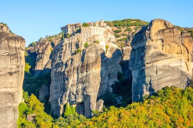 Греция. ясный летний день в метеоре. несколько зданий скального монастыря с красными крышами на фоне безоблачного голубого неба.