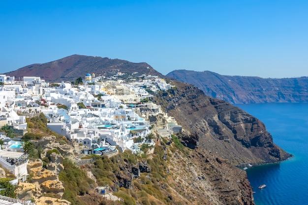 그리스. 산토리니 칼데라의 화려한 건물. 바위 해안에 화창한 여름 날