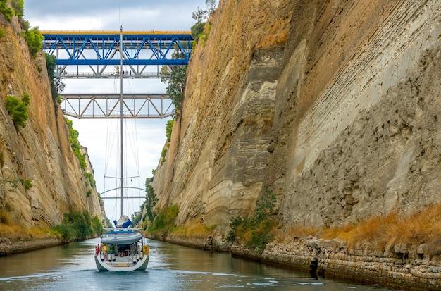 ギリシャ。曇りのコリントス運河。いくつかの橋。セーリングヨット。船尾の眺め