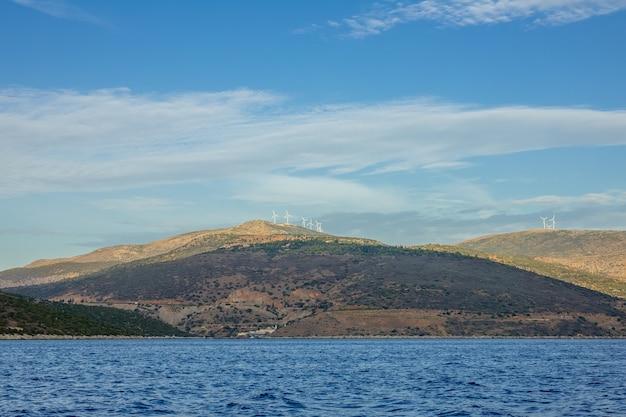 ギリシャ。コリントス湾。頂上に風力発電所がある丘陵地帯。ボートからの眺め