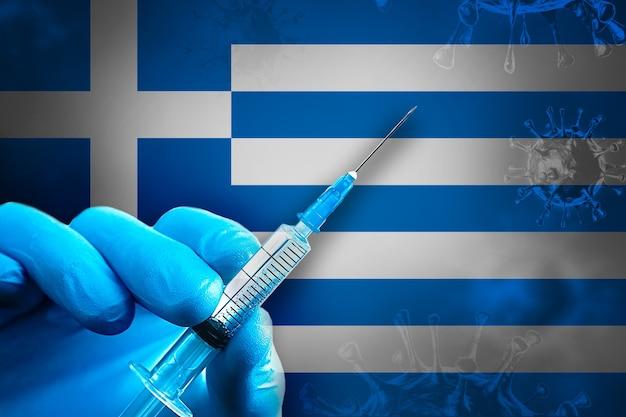 그리스 covid19 예방 접종 캠페인 파란색 고무 장갑을 끼고 깃발 앞에 주사기를 들고 있습니다.