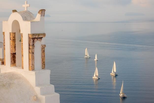 ギリシャ。サントリーニ島の夜。イアの十字架のあるギリシャの教会からセーリングヨットのある湾への眺め