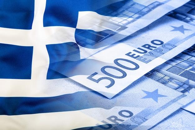 ギリシャの旗。ユーロマネー。ユーロ通貨。ユーロのお金の背景にカラフルな手を振るギリシャの旗