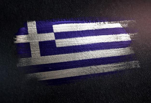 Greece flag made of metallic brush paint on grunge dark wall
