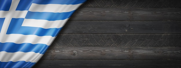 黒い木の壁にギリシャの旗。水平方向のパノラマバナー。