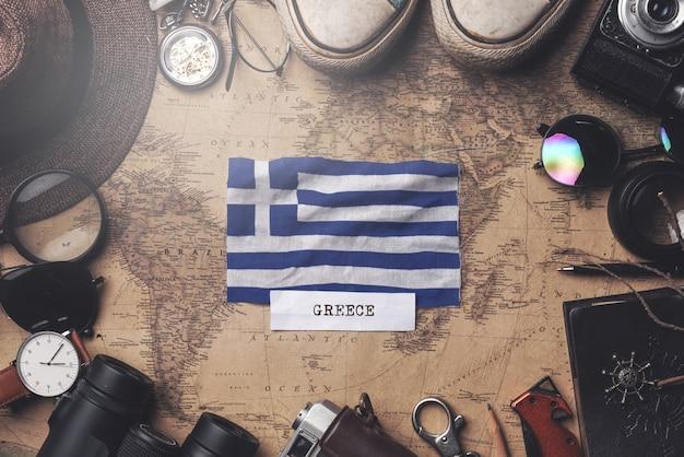 Greece flag between traveler's accessories on old vintage map. overhead shot